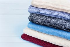 Wool sweaters and knitted winter clothes on blue wooden background. Copy space for text. Stock Photo