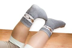 Wool thermal socks on a women`s legs on a wooden floor. Pair of the wool thermal socks on women legs on the wooden floor on a white background Royalty Free Stock Photos