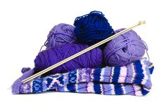 Wool to Knit a Sweater. Knitting yarn and needles rest on top of a knitting project, isolated Stock Photo