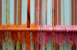 Wool weavings of many colors in the old textile loom Royalty Free Stock Images