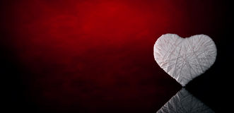 Wool white heart. On a dark red background. Valentine's Day Stock Photo
