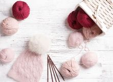Wool yarn in coils with knitting needles in wicker basket on background Stock Photo