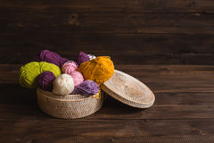 Wool yarn in coils with knitting needles in wicker Royalty Free Stock Image