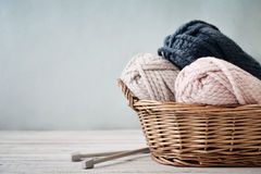 Wool yarn in coils. With knitting needles in wicker basket on light blue background stock photo