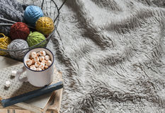 Wool yarn in vintage metal basket, old books and hot chocolate in a ceramic mug on light tissue surface. Stock Image