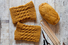 Wool yellow legwarmers, scissors, knitting needles and yarn Royalty Free Stock Images