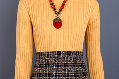 Wool yellow pullover with necklace. Sweater with accessorie, front view. Close up Stock Photo