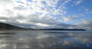 Woolacombe Beach. At low tide. Blue cloudy sky is reflected in the wet sand Stock Images