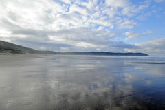 Woolacombe Beach UK. Woolacombe Beach, England at low tide. The dramatic sky is reflected in the wet sands Stock Photography