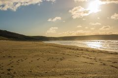 Woolacombe Sand near Barnstaple, Devon, England. Sandy beach at Woolacombe Sand near Barnstaple in North Devon, England. Contre-jour photograph against the sun Royalty Free Stock Image