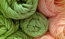 Balls of wool. Woolen balls in two colors, green and pink, clasped in a balls unevenly distributed stock photos