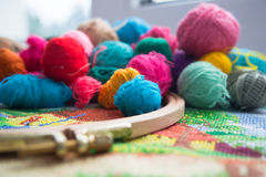 Woolen balls of yarn, tambour and embroidery. Stock Photos