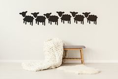 Woolen blanket on bench. Big, handmade, woolen blanket thrown on a grey bench standing under decorative paper sheep on the wall in simple interior royalty free stock photos