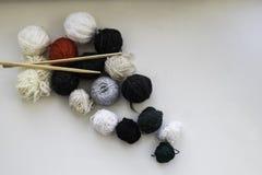 Woolen bollar och trästickor på den neutrala bakgrunden Lekmanna- lägenhet arkivbilder