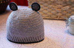 Woolen cap with teddy bear for child. Crochet handmade cute hat. Stock Images