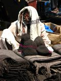 Woolen Caps and Blankets Seller. An old man sells woolen caps and blankets in summer sun in his streetside store, in India Royalty Free Stock Photo
