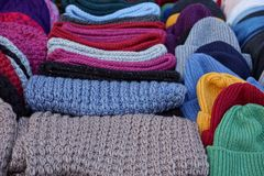 Colorful bright background of woolen fabric sweaters and hats. Woolen colored hats and sweaters in a shop window Stock Photography