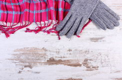 Woolen gloves and colorful shawl with copy space for text, old rustic wooden background Stock Photos