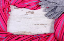 Woolen gloves and colorful shawl with copy space for text, old rustic wooden background Royalty Free Stock Photography