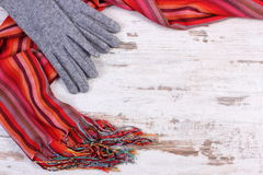 Woolen gloves and colorful shawl with copy space for text, old rustic wooden background Royalty Free Stock Image