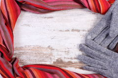 Woolen gloves and colorful shawl with copy space for text, old rustic wooden background Stock Photo