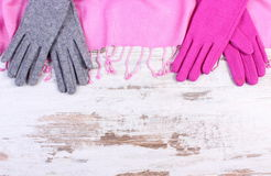 Woolen gloves and shawl with copy space for text, old rustic wooden background Royalty Free Stock Images
