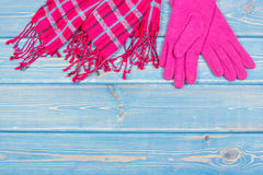 Woolen gloves and shawl for woman on blue boards, womanly clothing for autumn or winter, copy space for text. Woolen gloves and shawl for woman on blue boards Royalty Free Stock Image