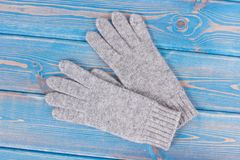 Woolen womanly gloves for autumn or winter on old blue boards. Woolen gloves for woman on old blue boards, womanly accessories for autumn or winter Stock Image