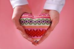 Woolen heart in hands Stock Photos
