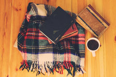 Woolen plaid, cup of coffee, old books on wooden background. Toned Royalty Free Stock Images