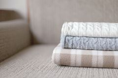 Some cozy plaids on a sofa. Autumn or winter concept. Woolen plaids or sweaters on a grey sofa, winter or autumn season Stock Photos