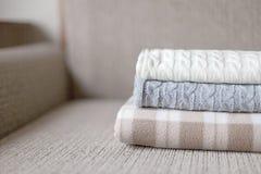 Some cozy plaids on a sofa. Autumn or winter concept. Stock Photos