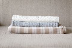Some cozy plaids on a sofa. Autumn or winter concept. Woolen plaids or sweaters on a grey sofa, winter or autumn season Stock Photography