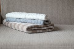 Some cozy plaids on a sofa. Autumn or winter concept. Royalty Free Stock Photos