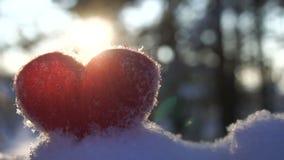 Woolen röd hjärta på snön och backlighted av ultrarapiden för vinterinställningssol