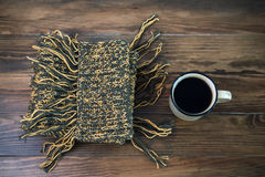 Woolen scarf and hot coffee on a wooden table Royalty Free Stock Images