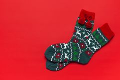 Woolen socks with a Christmas New Year ornament on red background top view flat lay. Holiday concept, Festive socks, presents Xmas. Congratulations background stock images