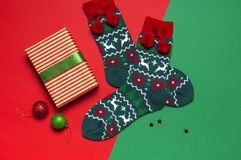 Woolen socks with a Christmas New Year ornament on red background top view flat lay. Holiday concept, Festive socks, presents Xmas. Congratulations background stock image