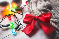 Woolen sweater and red bow with some colorful Christmas lights. On a wooden background Royalty Free Stock Photography