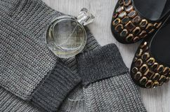 Woolen sweatshirt ,Women`s shoes and a bottle of perfume. Composition, Woolen sweatshirt , women`s shoes with colorful rhinestones and a bottle of perfume on a Royalty Free Stock Photos
