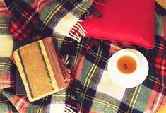 Woolen szkocka krata, filiżanka herbata, stare książki, czerwona poduszka na drewnianym tle Odgórny widok stonowany Obraz Stock