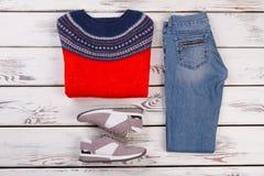 Woolen tröja, jeans och gymnastikskor Arkivbild