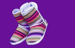 Woolen uggs with colored stripes on a purple background stock image