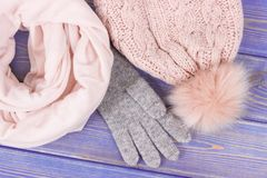 Woolen womanly gloves, cap and shawl for autumn or winter on old boards. Woolen womanly gloves, cap and shawl on old boards, clothing and accessories for autumn Royalty Free Stock Images