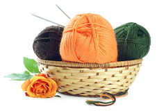 Woolen yarn. Three clews of woolen yarn in wicker basket  and tea rose over pure white background Stock Photo
