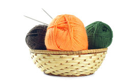 Woolen yarn. Three clews of woolen yarn in wicker basket over pure white background Royalty Free Stock Photo