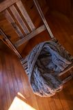 Woollen scarf lying on wooden chair Royalty Free Stock Photo