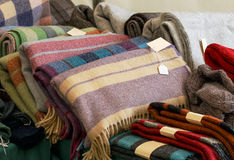 Woollen throws. Selection of throws traditionally made of wool in a pile for sale at market traders, great example of crafting industry Royalty Free Stock Photo