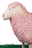 Woolly pink toy sheep. Closeup of the head of a kids woolly pink toy sheep or spring lamb with a textured fleece and wooden legs standing on green grass royalty free stock photo