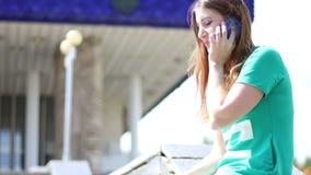 年轻wooman美丽的可爱的女孩发表演讲关于她的手机与朋友,当坐在公园时 股票录像